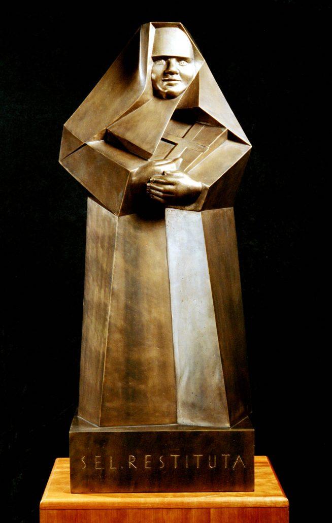 """Bronzestatue: Restituta mit Kreuz, auf Sockel mit Aufschrift """"sel. Restituta"""""""