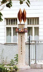 """Foto: Säule mit Aufschrift """"Restituta"""" und einem Kreuz, umgeben von einem bunten Ring"""