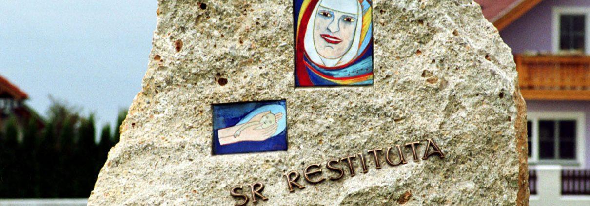 """Foto: Stein mit Inschrift """"Sr Restituta"""" und Bunten Bildern von Restituta und einer Hand, die ein Kind hält"""