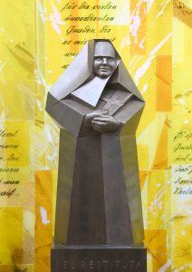 Metallfigur der Schwester Restituta mit Bibel im Arm